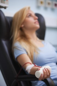 Woman sitting back while getting dialysis in hospital